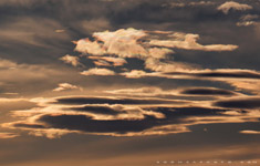 Glints of iridescence light foothills wave clouds over western Alberta - Feb.2, 2011
